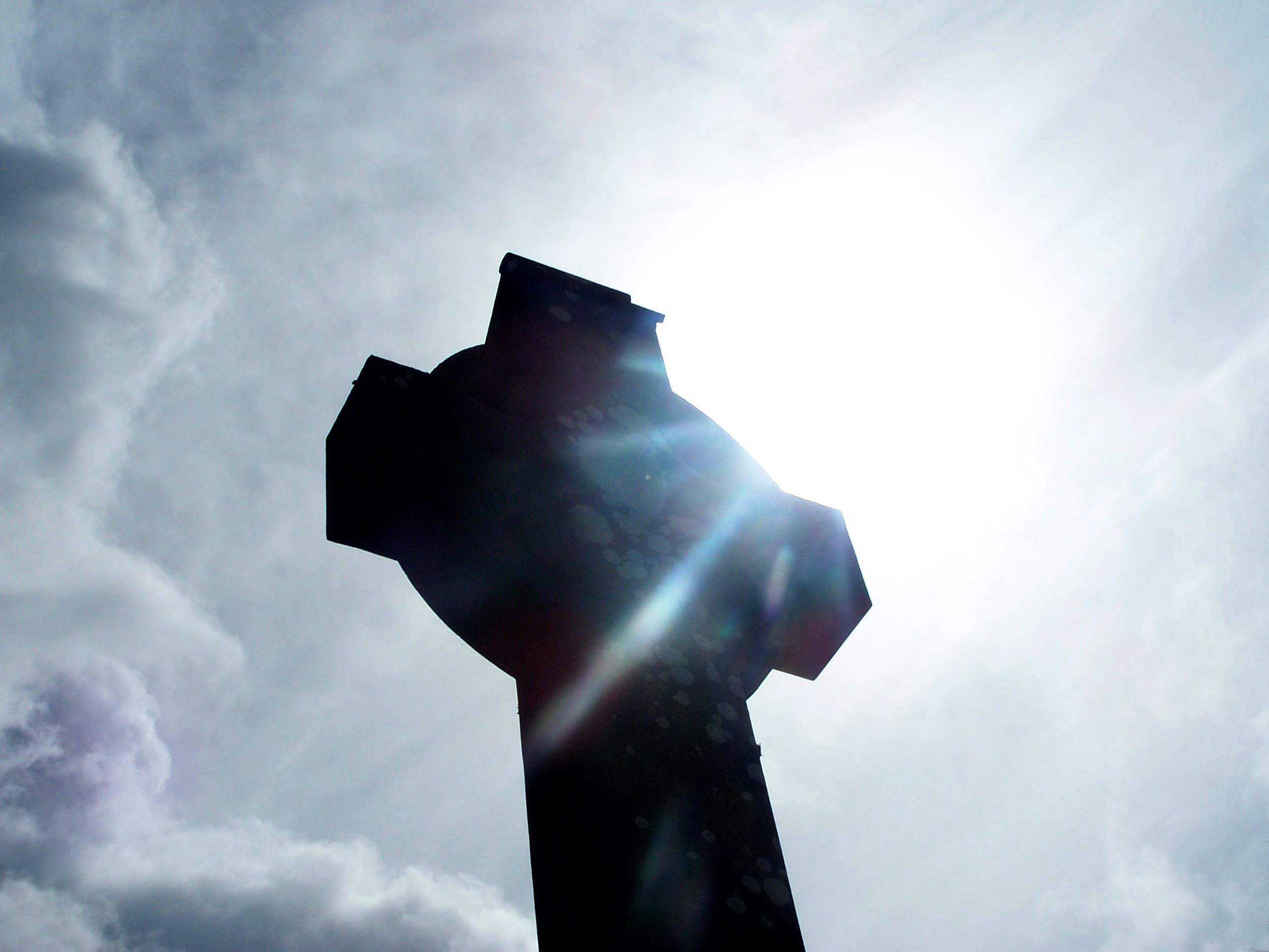 Cross - grave stone with light beaming through!